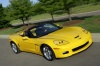 Driving 2010 Chevrolet Corvette Grand Sport Convertible in Velocity Yellow Tintcoat from a front right three-quarter view