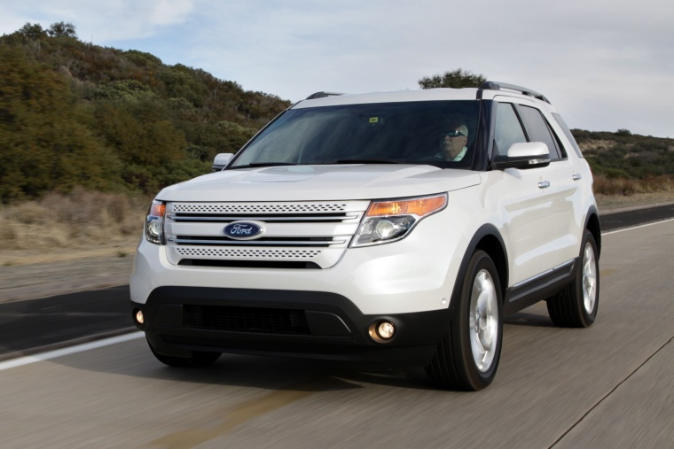 Driving 2013 Ford Explorer Limited 4WD in White Suede from a front left view