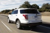 Driving 2013 Ford Explorer Limited 4WD in White Suede from a rear left view