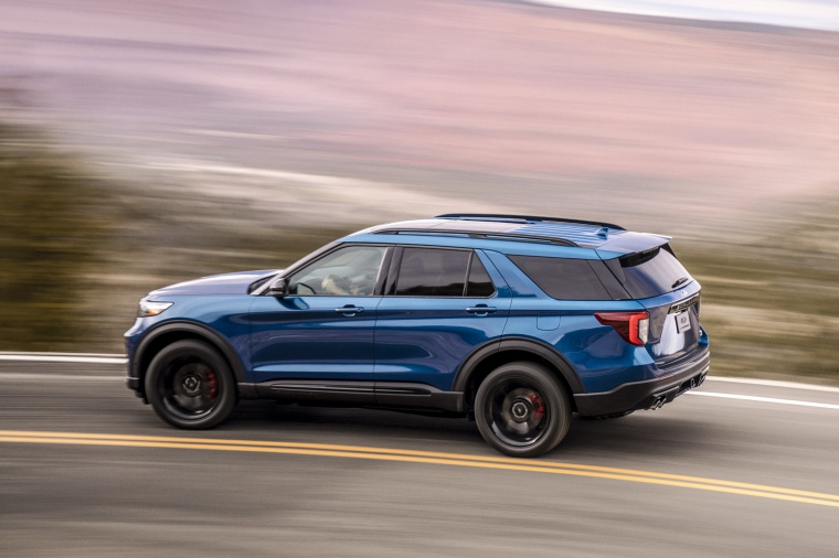 Driving 2020 Ford Explorer ST EcoBoost 4WD in Atlas Blue Metallic from a rear left three-quarter view