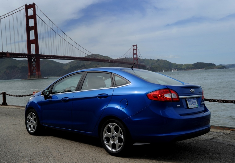2012 Ford Fiesta Sedan in Blue Flame Metallic from a rear left view