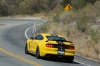 Driving 2016 Shelby GT350 R in Triple Yellow Tri-Coat from a rear left view