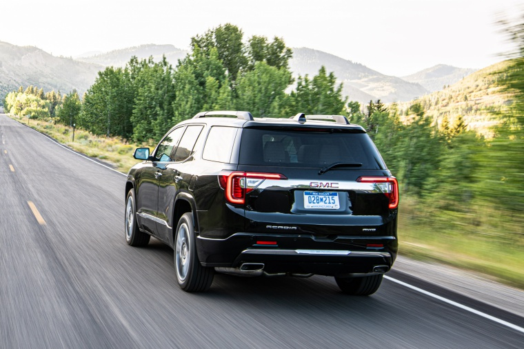 Driving 2020 GMC Acadia Denali AWD in Carbon Black Metallic from a rear left view