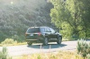 Driving 2020 GMC Acadia Denali AWD in Carbon Black Metallic from a rear right view