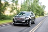 Driving 2020 GMC Acadia Denali AWD in Carbon Black Metallic from a front left view