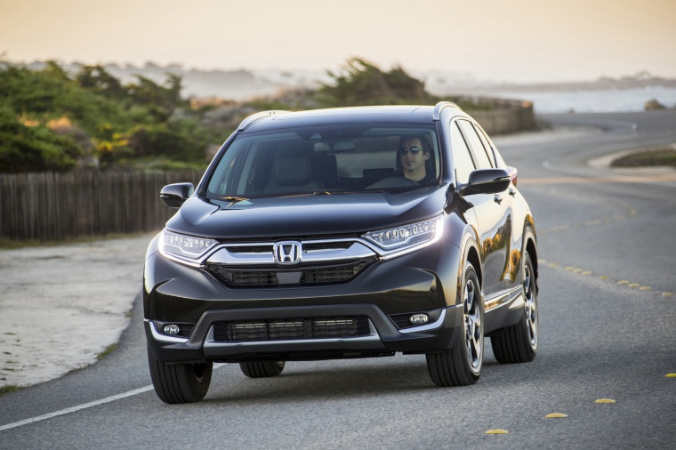Driving 2019 Honda CR-V Touring AWD in Crystal Black Pearl from a front left view