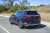 Driving 2019 Honda CR-V Touring AWD in Crystal Black Pearl from a rear left view