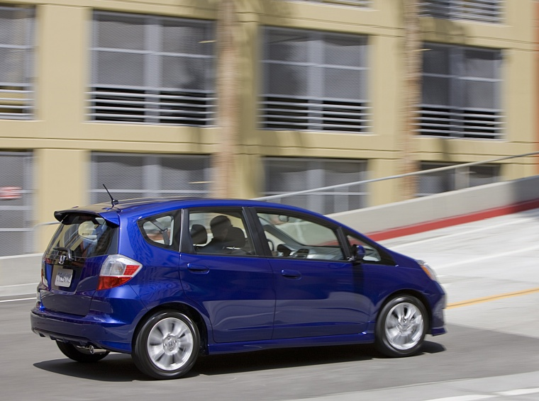 Driving 2010 Honda Fit Sport in Blue Sensation Pearl from a rear right three-quarter view