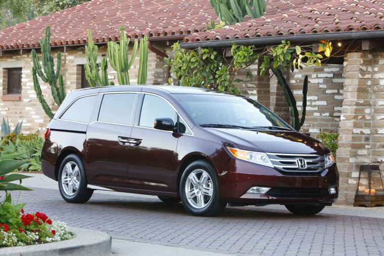 2011 Honda Odyssey Touring in Dark Cherry Pearl from a front right three-quarter view