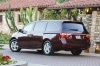 2011 Honda Odyssey Touring in Dark Cherry Pearl from a rear left three-quarter view