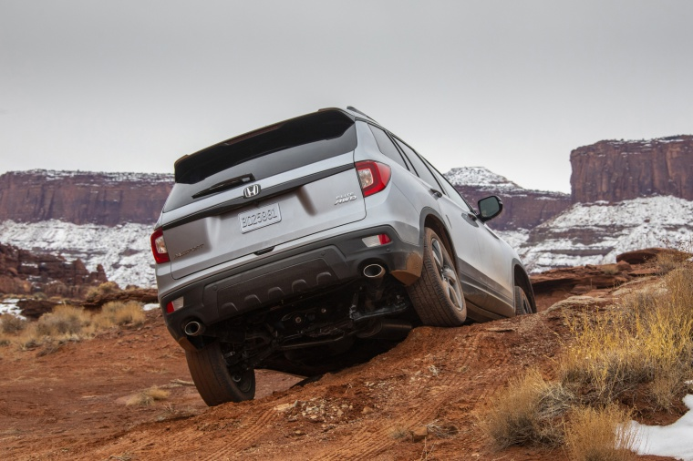 Driving 2020 Honda Passport Elite AWD in Lunar Silver Metallic from a rear view