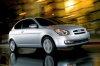 Driving 2010 Hyundai Accent Hatchback in Platinum Silver Pearl from a front right three-quarter view