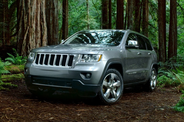 Driving 2013 Jeep Grand Cherokee in Bright Silver Metallic Clearcoat from a front left view