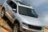 Driving 2013 Jeep Grand Cherokee in Bright Silver Metallic Clearcoat from a front right view