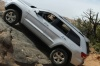 Driving 2013 Jeep Grand Cherokee in Bright Silver Metallic Clearcoat from a side view