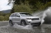 Driving 2013 Jeep Grand Cherokee in Bright Silver Metallic Clearcoat from a front right three-quarter view