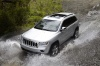 Driving 2013 Jeep Grand Cherokee in Bright Silver Metallic Clearcoat from a front left three-quarter top view