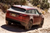Driving 2019 Land Rover Range Rover Velar P250 SE R-Dynamic in Firenze Red Metallic from a rear right view