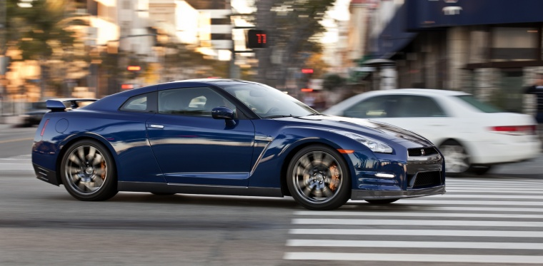 Driving 2014 Nissan GT-R Coupe in Deep Blue Pearl from a right side view