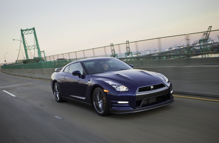 Driving 2014 Nissan GT-R Coupe in Deep Blue Pearl from a front right three-quarter view