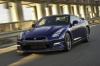 Driving 2014 Nissan GT-R Coupe in Deep Blue Pearl from a front left three-quarter view