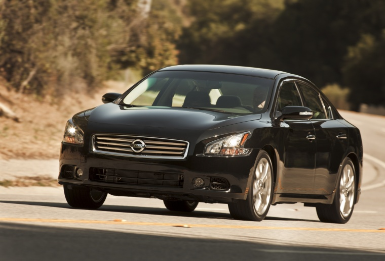 Driving 2013 Nissan Maxima in Crimson Black Metallic from a front left three-quarter view