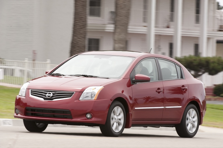 Driving 2010 Nissan Sentra SL Sedan in Red Brick Pearl from a front left three-quarter view