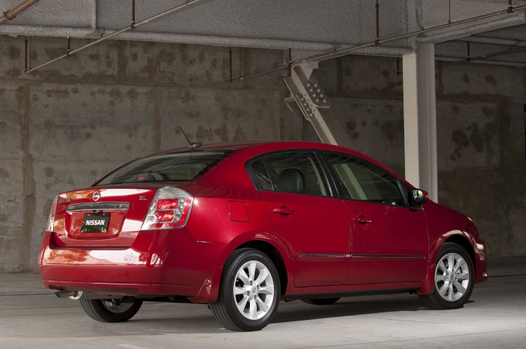 2010 Nissan Sentra SL Sedan in Red Brick Pearl from a rear right three-quarter view
