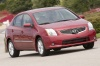 Driving 2010 Nissan Sentra SL Sedan in Red Brick Pearl from a front right three-quarter view