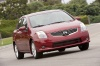 Driving 2010 Nissan Sentra SL Sedan in Red Brick Pearl from a front right view