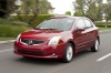 Driving 2010 Nissan Sentra SL Sedan in Red Brick Pearl from a front left view