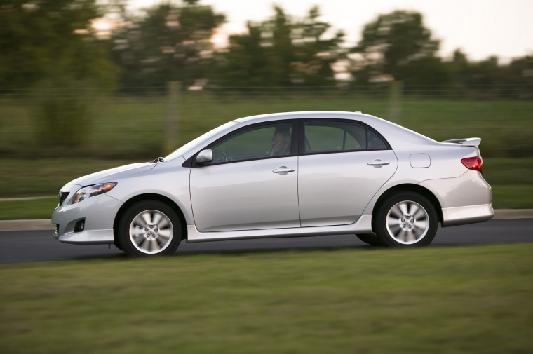 Driving 2010 Toyota Corolla XLE in Classic Silver Metallic from a side view