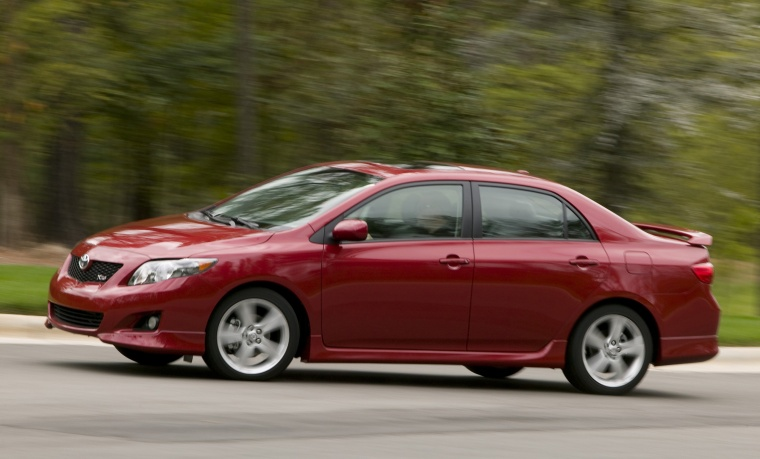Driving 2010 Toyota Corolla XRS in Barcelona Red Metallic from a left side view