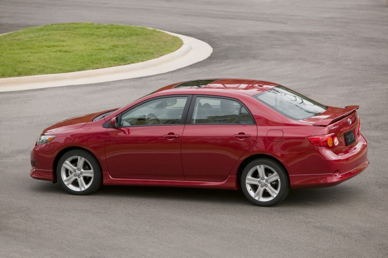 Driving 2010 Toyota Corolla XRS in Barcelona Red Metallic from a rear left three-quarter view