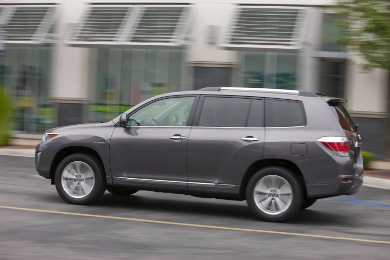 Driving 2013 Toyota Highlander Hybrid in Magnetic Gray Metallic from a rear left three-quarter view