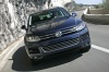 Driving 2013 Volkswagen Touareg Hybrid in Night Blue Metallic from a frontal view
